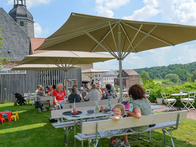 Blümchen Café Rochlitz Blick auf Terrasse mit Gästen unter Sonnenschirmen bei schönem Sommerwetter