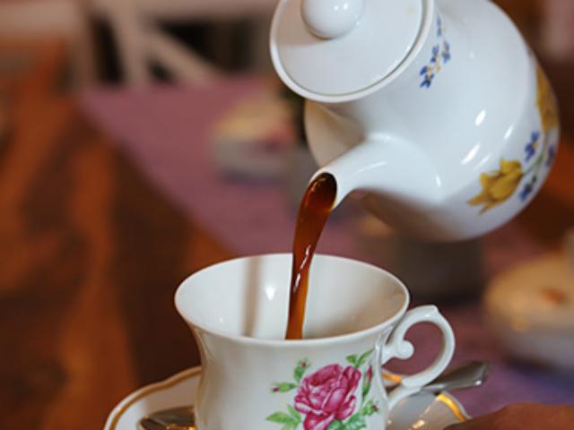 Blümchen Café Rochlitz Kaffee wird aus einer Porzellankanne mit Blümchen in eine Tasse mit floralem Muster eingegossen