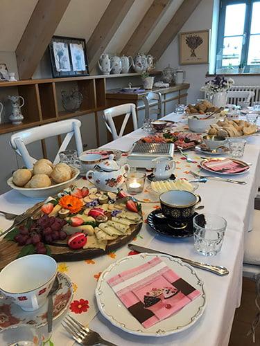 Blümchen Café Rochlitz gemütlich gedeckter Brunchtisch mit frischen Brötchen, Belag und angezündeten Kerzen
