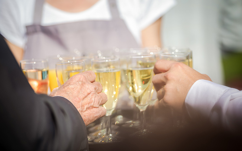 Blümchen Café Rochlitz zwei Personen greifen sich ein Sektglas von einem Tablett mit vielen weiteren Sektgläsern, das von einer Dame gehalten wird
