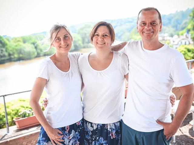 Blümchen Café Rochlitz Team Therés Meier, Sarah Kroth & Frederik Hendler lächeln in die Kamera mit Zwickauer Mulde im Hintergrund bei Sonnenschein