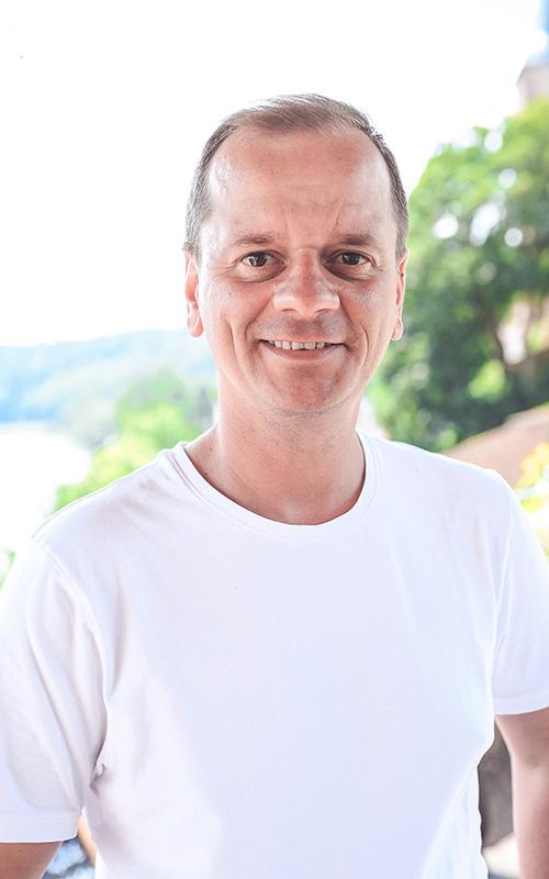Blümchen Café Rochlitz Frederik Hendler mit weißem T-Shirt lacht in die Kamera mit Zwickauer Mulde im Hintergrund bei Sonnenschein