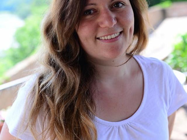 Blümchen Café Rochlitz Sarah Kroth mit weißem T-Shirt lacht in die Kamera mit Zwickauer Mulde im Hintergrund bei Sonnenschein