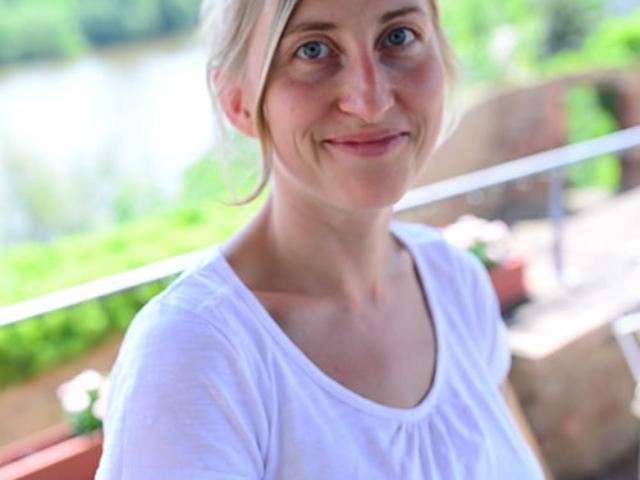 Blümchen Café Rochlitz Therés Meier mit weißem T-Shirt lacht in die Kamera mit Zwickauer Mulde im Hintergrund bei Sonnenschein